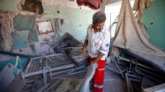 A Palestinian Red Crescent medic collects items from a hospital room damaged by Israeli shelling in central Gaza.