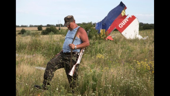 A pro-Russian rebel passes wreckage from the crashed jet near Hrabove on Monday, July 21, 2014.