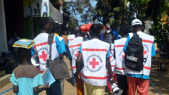 People can be infected by others if they come into contact with body fluids from an infected person or contaminated objects from infected persons. Pictured, Guinean Red Cross members spread awareness about the Ebola virus.
