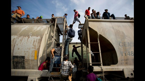 Central American migrants climb on a northbound train during their journey toward the U.S.-Mexico border in Ixtepec, Mexico, on Saturday, July 12.
