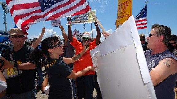 Demonstrators from opposing sides confront each other, Friday, July 4, 2014, outside a U.S. Border Patrol station in Murrieta, Calif. Demonstrators on both sides of the immigration debate had gathered where the agency was foiled earlier this week in an attempt to bus in and process some of the immigrants who have flooded the Texas border with Mexico. (AP Photo/Mark J. Terrill/AP Photo)