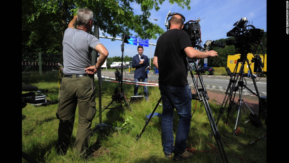 As they wait for victims' bodies to arrive on July 23, members of the media report in front of a military airport in Eindhoven.