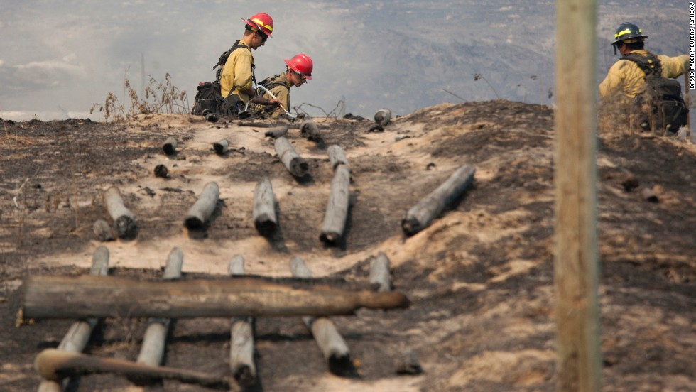 "Firefighters work in a field near a burnt fence Sunday, July 20, near Brewster, Washington. <a href=""http://www.cnn.com/2014/07/20/us/pacific-northwest-wildfires/index.html"">Nearly a million acres</a> were burning Sunday as 21 wildfires raged in the Pacific Northwest, fire officials said."