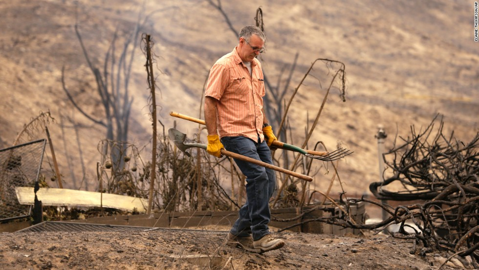 David Burdick walks past the smoldering remains of his niece's home after sifting through the rubble July 18 in Pateros.