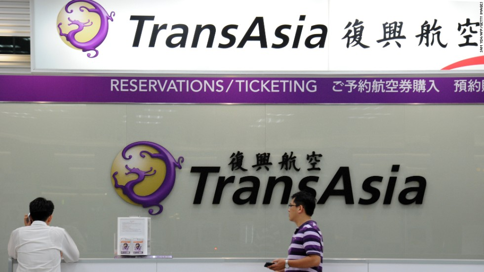 Local journalists wait in front of a TransAsia reservations desk at the Taipei Sungshan Airport in Taipei, Taiwan, on July 23.