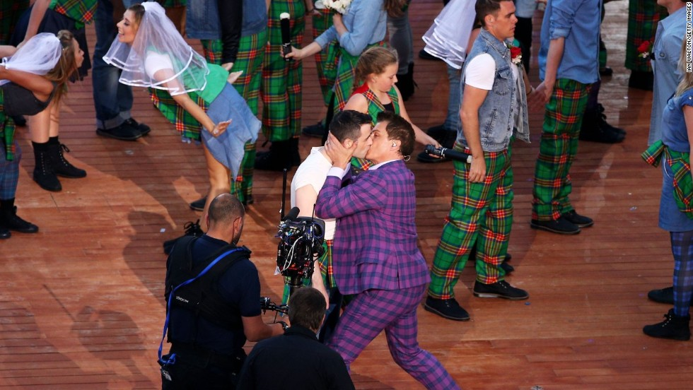 Actor and singer John Barrowman kisses another performer during the opening ceremony of the Glasgow 2014 Commonwealth Games on July 23, 2014.