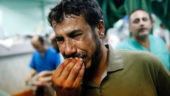 A Palestinian man cries after bringing a child to the Kamal Adwan hospital in Beit Lahiya on Thursday, July 24. The child was wounded in a strike on a school that was serving as a shelter for families in Gaza. It