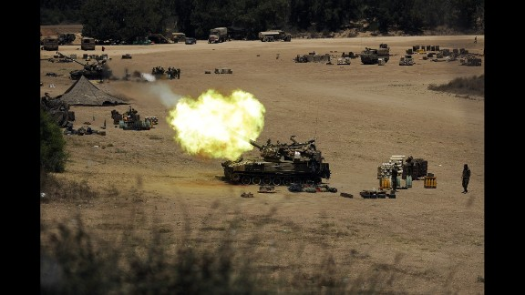 An Israeli tank fires toward Gaza from a position near Israel