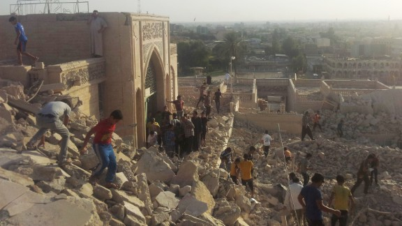 People walk on the rubble of the destroyed Mosque of the Prophet Yunis (Arabic for Jonah) in Mosul, Iraq, on Thursday, July 24. Militants belonging to the Islamic State in Iraq and Syria, or ISIS, planted explosives around the tomb and detonated the explosion remotely, civil defense officials told CNN.