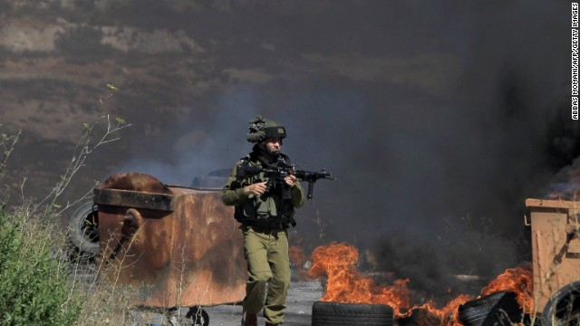 An armed Israeli soldier walks past burning tires during clashes with Palestinians at the gates of Beit El Jewish settlement in the Israel occupied West Bank near Ramallah following a march organised by the Palestinian Islamic movement Hamas towards the settlement on July 25, 2014. Five Palestinians were killed in the West Bank on July 25, 2014 in two separate incidents involving both Israeli troops and Israeli settlers, Palestinian security sources told AFP.    AFP PHOTO / ABBAS MOMANI        (Photo credit should read ABBAS MOMANI/AFP/Getty Images)