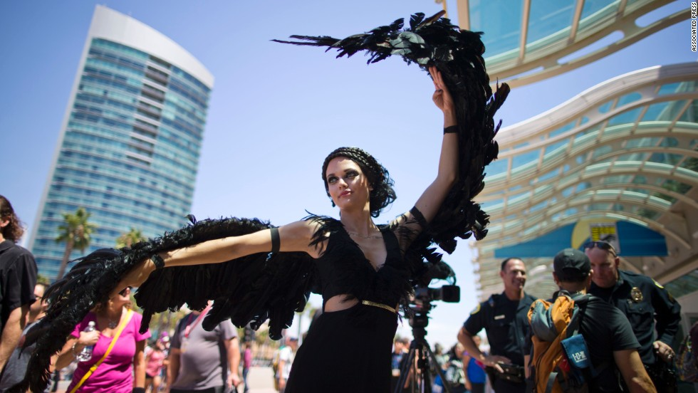 "A woman dressed as the character Katniss Everdeen from the movie ""The Hunger Games: Catching Fire"" poses in front of Comic-Con on July 24."