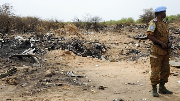 """A United Nations soldier stands at the crash site of Air Algerie Flight 5017 on Saturday, July 26. A U.N. spokeswoman says a second flight data from the DC-83 was recovered on Saturday. The flight, carrying 116 people when it took off from Burkina Faso on July 24 bound for Algiers, crashed in Mali's Gossi region, west of Gao. """"Regrettably, there were no survivors,"""" said French President Francois Hollande."""