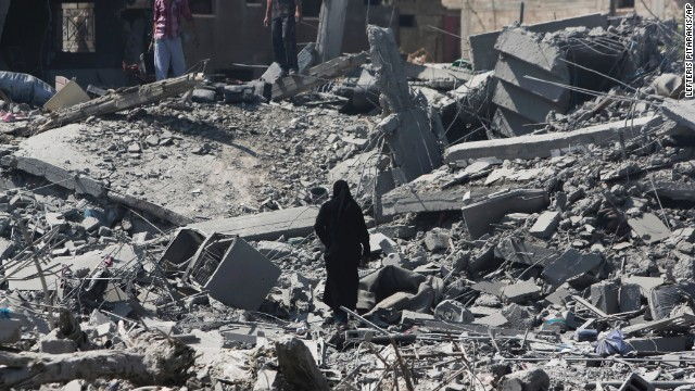 Palestinians through rubble on July 26 in Beit Hanoun.