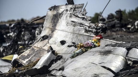 caption:This photo taken on July 26, 2014 shows flowers, left by parents of an Australian victim of the crash, laid on a piece of the Malaysia Airlines plane MH17, near the village of Hrabove (Grabove), in the Donetsk region. Ukraine sought on July 25 to avoid a political crisis after the shock resignation of its prime minister, as fighting between the army and rebels close to the Malaysian airliner crash site claimed over a dozen more lives. Dutch and Australian forces were being readied on July 26 for possible deployment to secure the rebel-held crash site of the Malaysia Airlines flight MH17 in east Ukraine where many victims