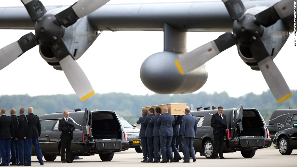 Dutch military personnel carry coffins to a waiting hearse at the Eindhoven airbase on Friday, July 25.