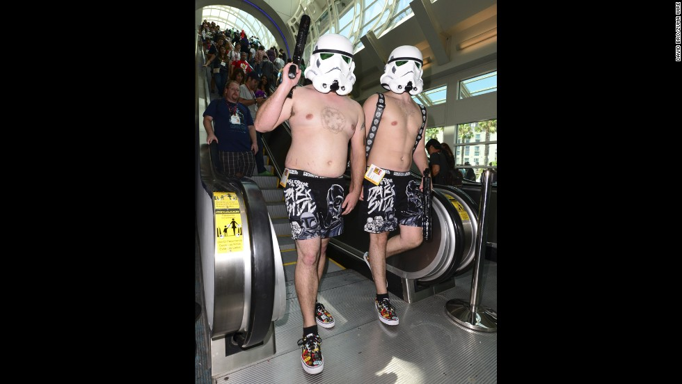 Two shirtless stormtroopers patrol the convention hall.