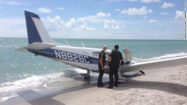 Sarasota County Sheriff's Office officials look over a plane that hit a father and daughter Sunday on a Florida beach.