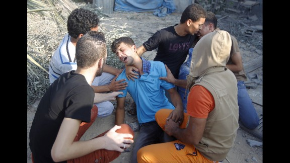 Near the rubble of their home in Rafah, Palestinian men mourn July 29 for people killed during an airstrike.