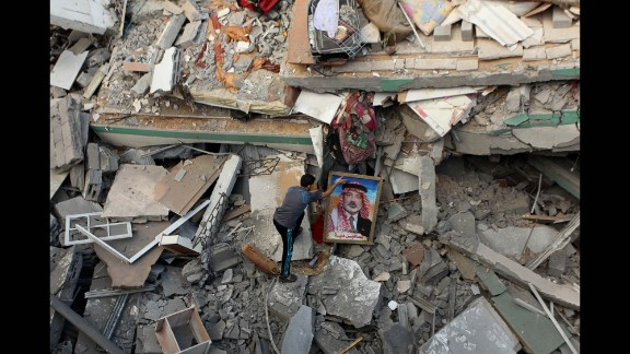 A Palestinian man places a portrait of Hamas leader Ismail Haniya on the rubble of Haniya