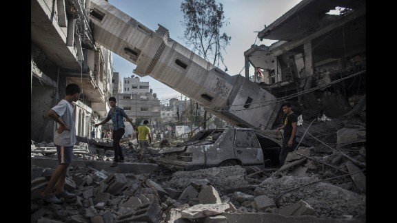 Palestinians walk under the collapsed minaret of a destroyed mosque in Gaza City on July 30.
