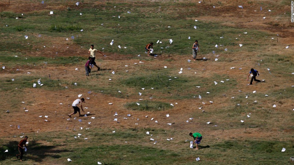 Palestinians gather leaflets that fell from an Israeli plane on July 30. The leaflets warned residents of airstrikes in Gaza City.