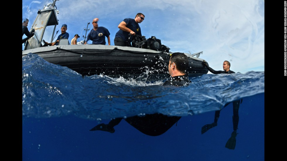 U.S. Navy divers from the Mobile Diving and Salvage Unit assist U.S. Coast Guard divers during an exercise on July 9.