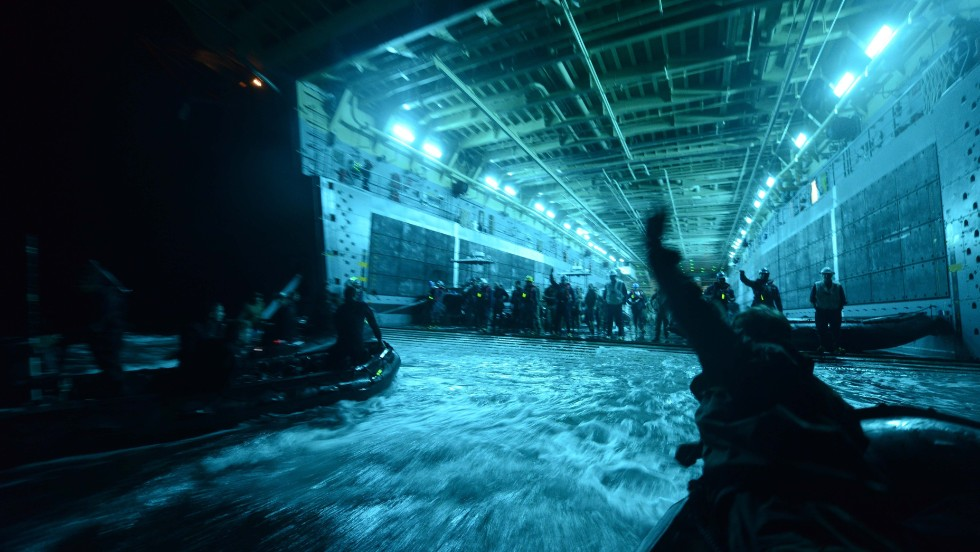 Members of the militaries of New Zealand, the Netherlands, Canada, Japan, Australia and Chile recover their boats into the well deck of the amphibious transport dock USS Anchorage after conducting night dive exercises off the coast of San Diego on July 18.