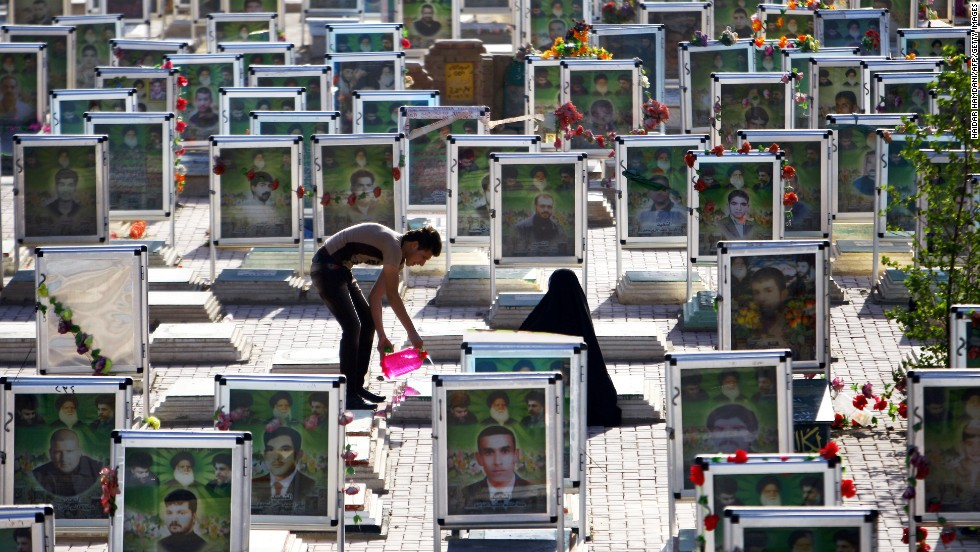 "Iraqi Shiites clean the grave of a relative at one of the world's biggest cemeteries in the holy city of Najaf on Tuesday, July 29, during the Eid al-Fitr celebrations marking the end of the Muslim fasting month of <a href=""http://religion.blogs.cnn.com/2014/06/28/the-belief-blog-guide-to-ramadan/"" target=""_blank"">Ramadan</a>."