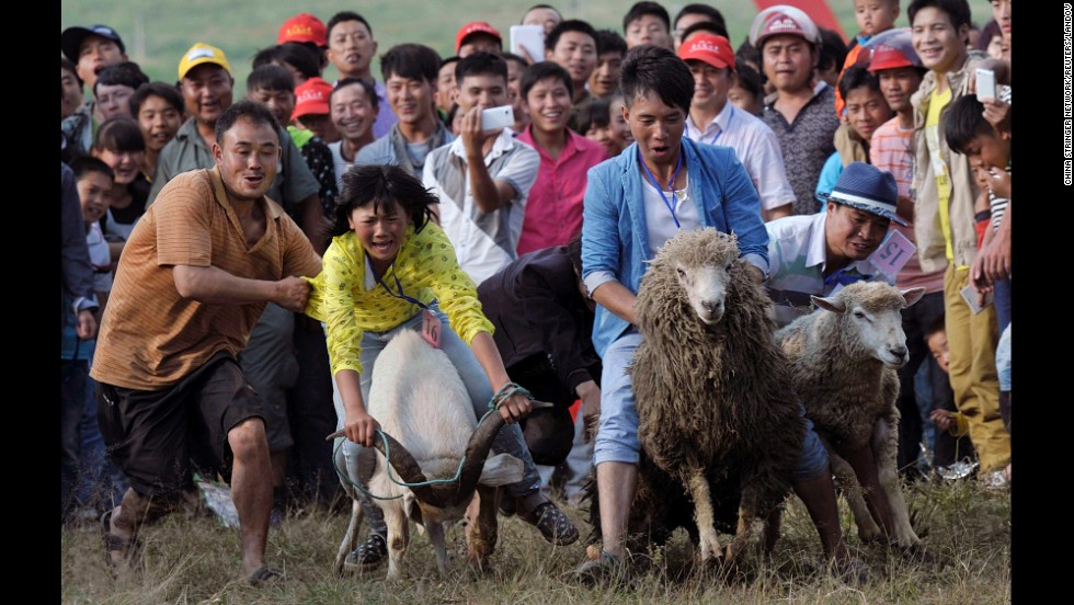 Contestants ride goats and sheep during a race to celebrate a festival in Fengshan, Guizhou province, China, on Saturday, July 26.