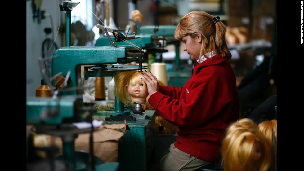An employee sews a doll's hair to its head inside the toy factory in Buenos Aires on Monday, July 28.