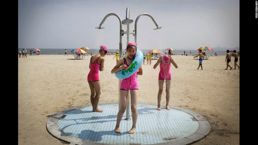 North Korean girls in similar bathing suits stand under a shower at the Songdowon International Children's Camp on Tuesday, July 29 in Wonsan, North Korea.