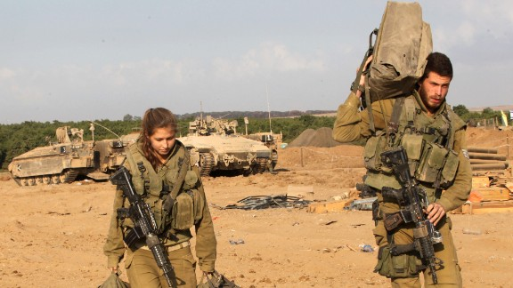 Israeli soldiers walk out from their armoured personnel carriers on August 3, along the border between Israel and Gaza after they pulled out from Gaza.