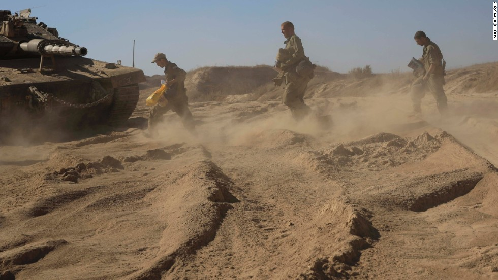 Israeli soldiers walk to their tank at a staging area near the border with Gaza on August 2.