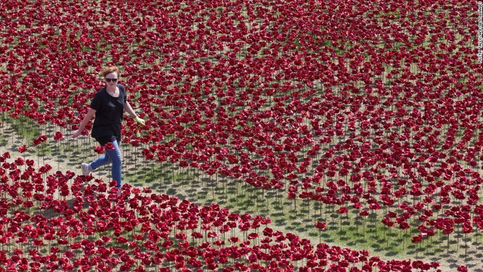 A woman walks through the ceramic poppies on Sunday, August 3.