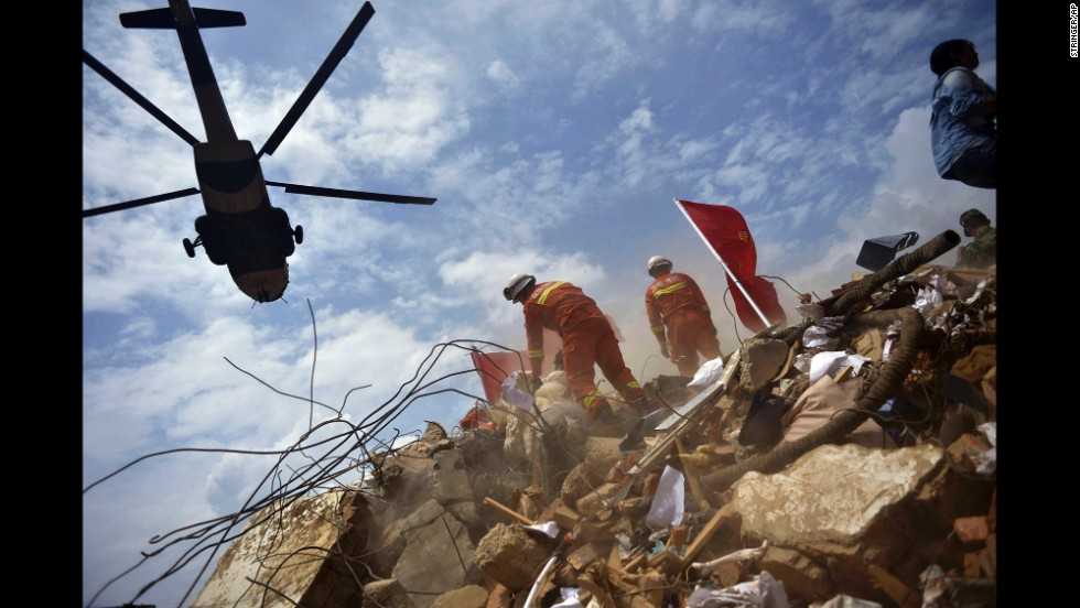A helicopter flies over rescue workers Monday, August 4, in Longtoushan.