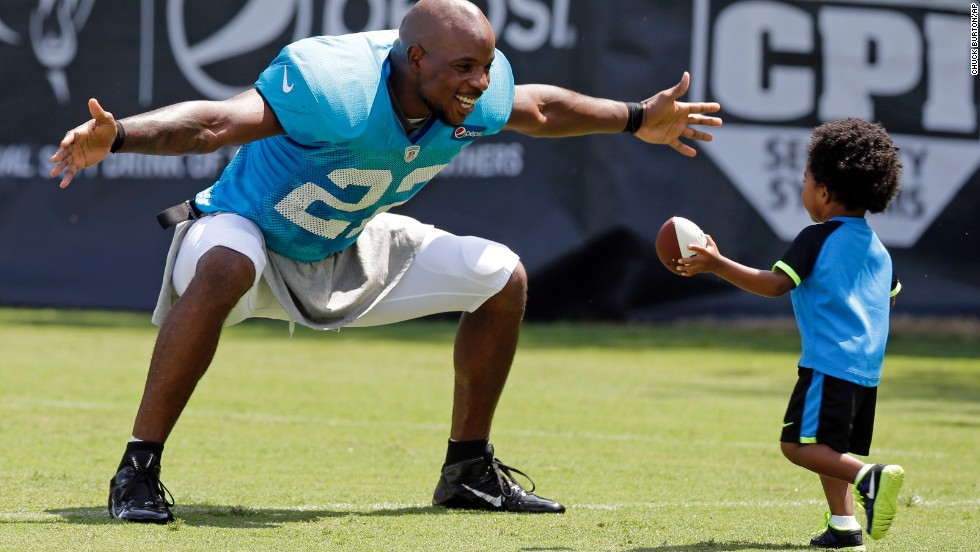 Josh Thomas of the NFL's Carolina Panthers reaches out to hug his son, Dallas, after a practice Tuesday, July 29, in Spartanburg, South Carolina.