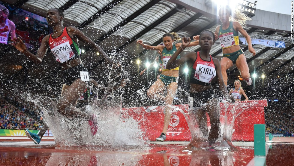 Kenya's Purity Cherotich Kirui and Milcah Chemos Cheywa lead runners through a water jump in the final of the 3,000-meter steeplechase Wednesday, July 30, at the Commonwealth Games in Glasgow, Scotland. Kurui won the event while Cheywa took silver.