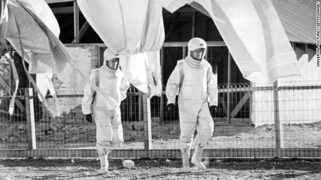 (L-R) James Olson and Arthur Hill walking in protective suits in a scene from the 1971 film 'The Andromeda Strain.' (Photo by Universal Pictures/Getty Images)