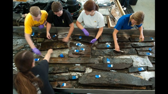 Volunteers and curators from the Maryland Archeological Conservation Laboratory clean timbers from the ship in August 2010. For more than 200 years, the ship was beneath New York City