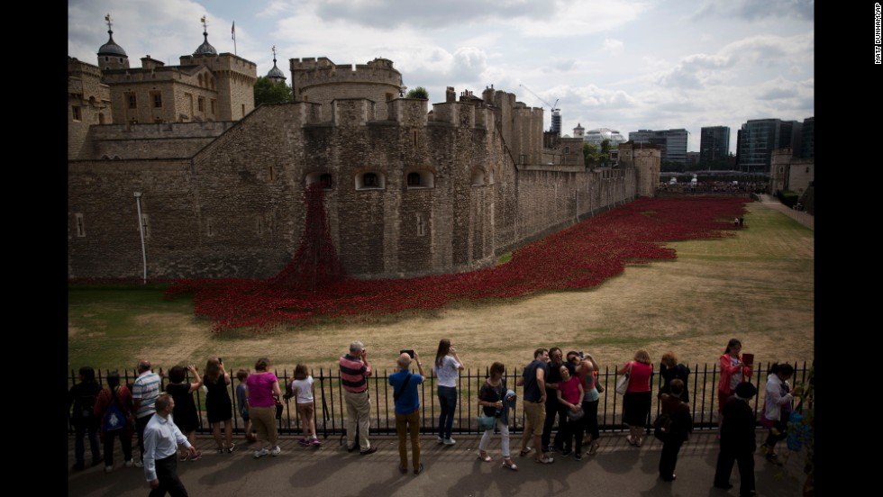 "People pose for a selfie Tuesday, August 5, in front of the Tower of London, where <a href=""http://www.cnn.com/2014/08/04/europe/gallery/tower-of-london-art-installation/index.html"">a special art installation</a> is being built to commemorate the 100th anniversary of World War I. There will be 888,246 ceramic poppies planted, one for each British military member that died during the war. The installation, called ""Blood Swept Lands and Seas of Red,"" was created by artist Paul Cummins."