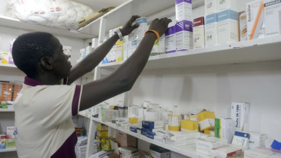 A pharmacist searches for drugs in a pharmacy in Lagos on July 26, 2014.
