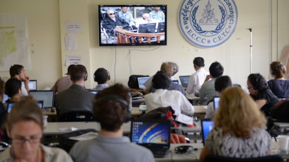 """Cambodian and international journalists watch a live video feed showing the verdicts in the trial of former Khmer Rouge leader """"Brother Number Two,"""" Nuon Chea, and former Khmer Rouge head of state Khieu Samphan, August 7, 2014."""