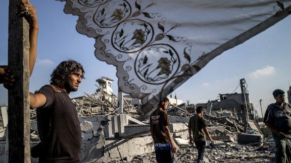Palestinians stand next to a makeshift shelter erected outside their destroyed house in the devastated neighbourhood of Shejaiya in Gaza City on August 6, 2014.