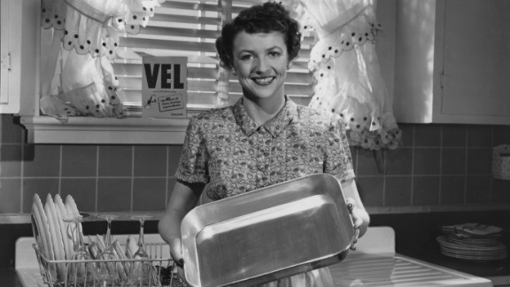 A 1960s housewife shows off her gleaming dishes.