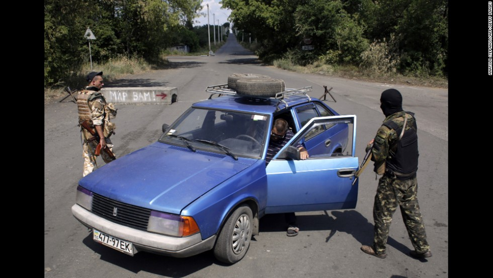 A man steps out of his car as Ukrainian soldiers inspect the vehicle at a checkpoint in Debaltseve on August 6.