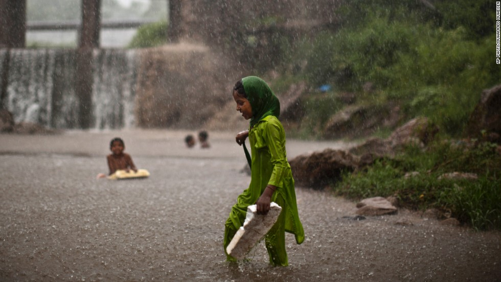 AUGUST 7 - ISLAMABAD, PAKISTAN: A young girl, wades through water looking for shelter from a sudden heavy rainfall after days of scorching temperatures due to a heat wave.