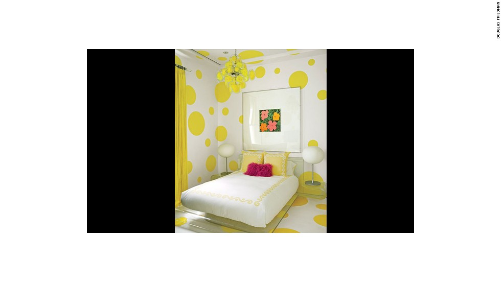"A Warhol ""Flowers"" work hangs in a guest room that's decked out in a dotted wall treatment devised by Martyn Lawrence Bullard and painted in a Benjamin Moore yellow; the vintage chandelier is by Vistosi, the bedding is by Leontine Linens, and the felt rug is by Anthony Monaco. See more images at <a href=""http://www.architecturaldigest.com/celebrity-homes/2014/dee-and-tommy-hilfiger-florida-beach-house-slideshow?mbid=synd_cnn"" target=""_blank"">ArchitecturalDigest.com</a>"