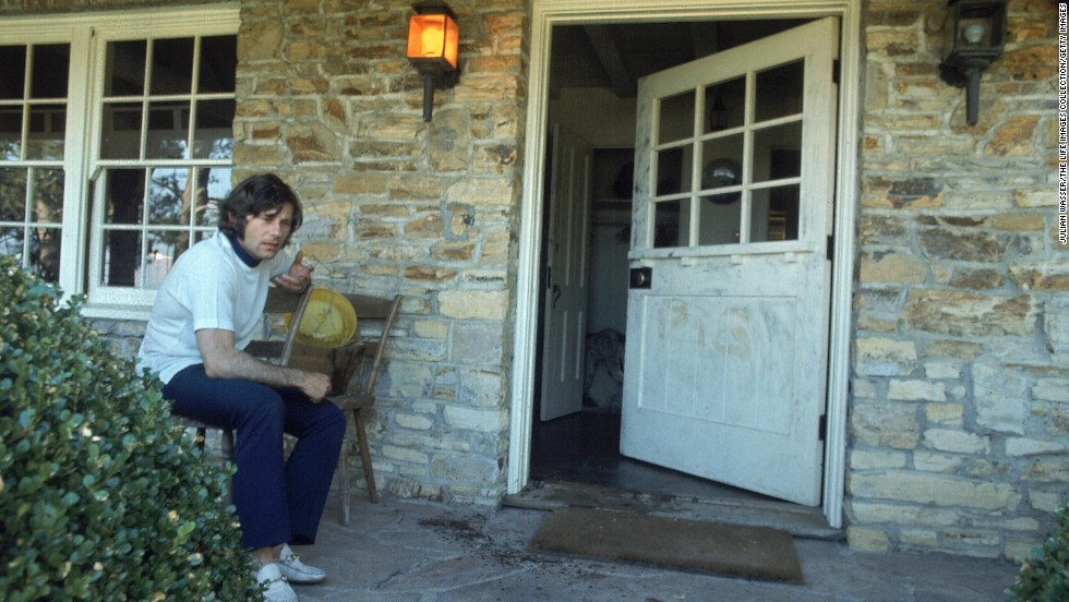 "Polanski, who was out of town at the time of the murders, is seen on the porch outside his home. The remnants of the word ""pig"" can be seen where it was scrawled on the door."