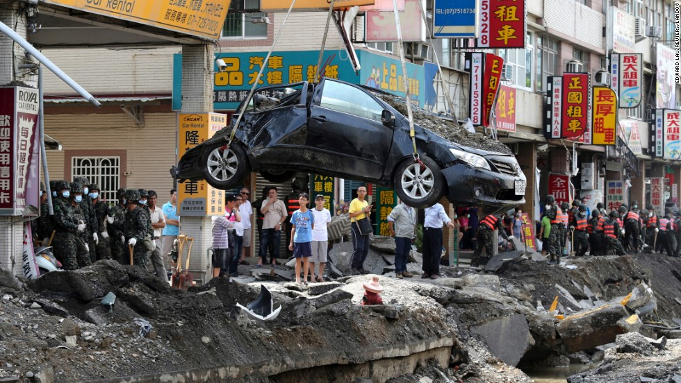 "A damaged car is removed from wreckage Saturday, August 2, in Kaohsiung, Taiwan. <a href=""http://www.cnn.com/2014/07/31/world/asia/taiwan-explosions/index.html"">A series of explosions,</a> triggered by gas leaks, killed at least 26 people and injured hundreds more, state news agency CNA reported."