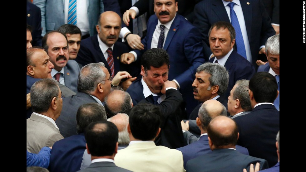 Muhyettin Aksak, a lawmaker from the ruling AK Party in Turkey, punches Sinan Ogan of the Nationalist Movement Party during a debate in parliament Monday, August 4, in Ankara, Turkey. Three members of parliament were injured when the debate turned into an all-out fistfight, the Dogan News Agency reported, and the session was adjourned. During the debate, the parties were discussing whether to establish an inquiry into the Islamist militants fighting in neighboring Iraq and Syria.